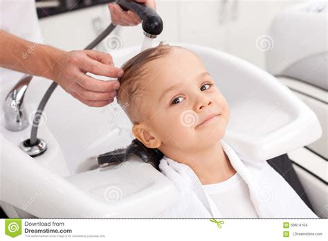 pretty verry young boys washing hairs cheerful male child is having hair washed in salon stock