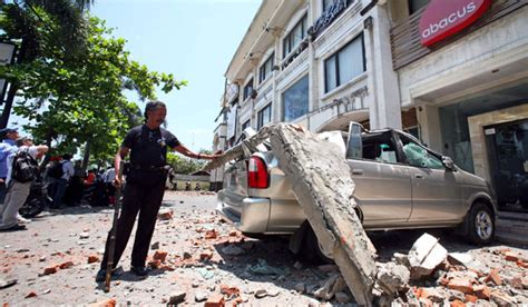 earthquake ubud bali a man examines a minivan destroyed by an earthquake in bali