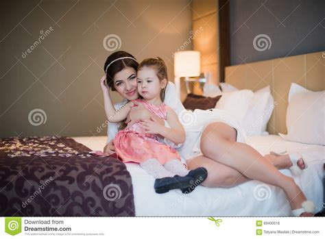 bed moms beautiful mother hugs daughter in the bedroom stock photo