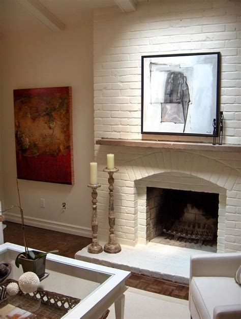 painting the brick fireplace the same color as the walls will totally change the look of the
