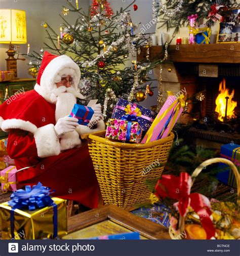 mr santa claus preparing christmas presents under the tree
