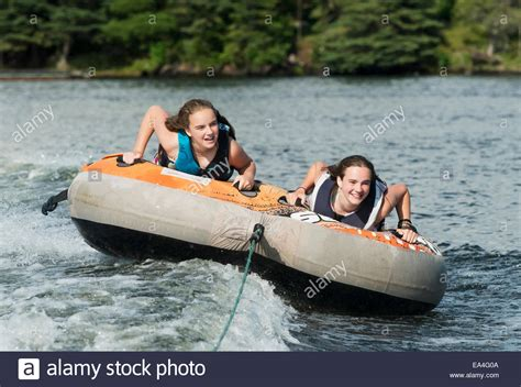two teenage girls riding in an inner tube being pulled by - Inner Tube Pulled By Boat