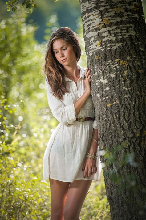beautiful woman by the tree looking up stock photo image attractive young woman in white short dress posing near a
