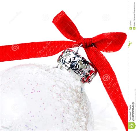 white christmas ball with red ribbon on a snow on white
