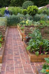 brick path through beautiful raised bed vegetable gardens