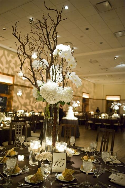 Some centerpieces will be in tall vases with branches n