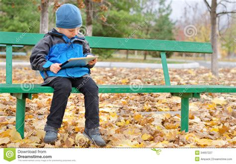 kid on bench little boy reading a tablet computer royalty free stock