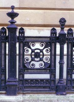 custom built iron gates in an deco fish scale motif replaced a solid door to lighten a once