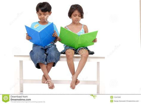 sister company of bench brother and sister reading books on bench stock