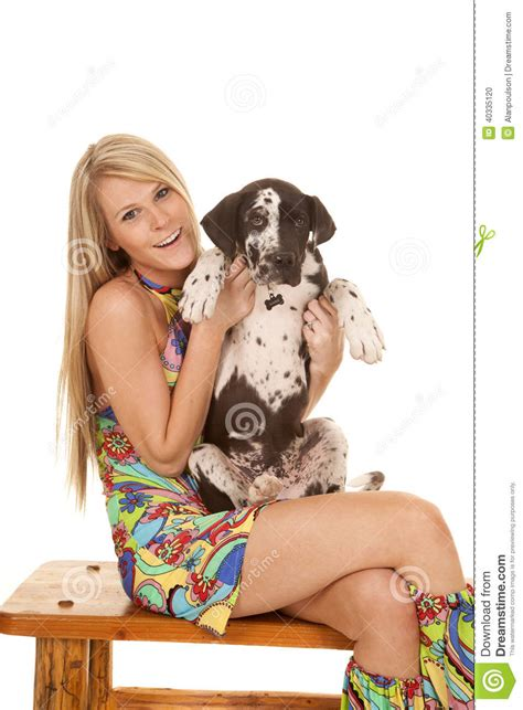 clothes her bench woman colorful dress sit hold dog up smiling stock photo