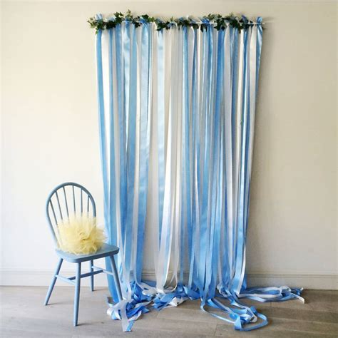 blue ribbon backdrop on white pole with ivy garland by