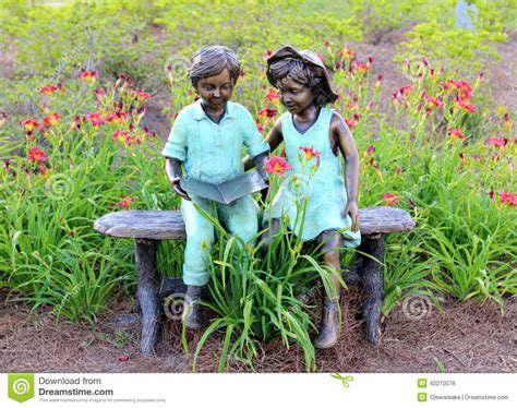little girl sitting on bench statue statue of two young children reading a book editorial
