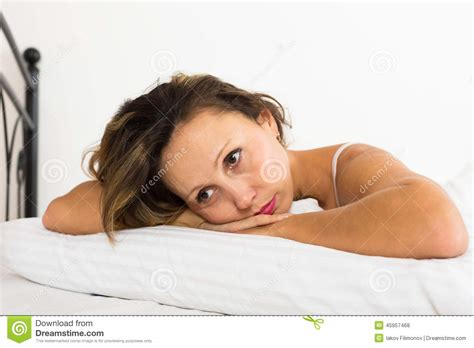 laying in bed upset woman laying in bed