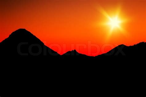 warm orange warm mountains sunset with orange sky silhouette of mountains stock photo colourbox