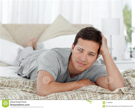 lying on the bed thoughtful young man lying on his bed stock photography