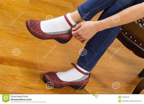 putting on shoes putting on causal shoes while sitting on footstool