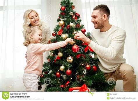 happy family decorating christmas tree at home stock photo