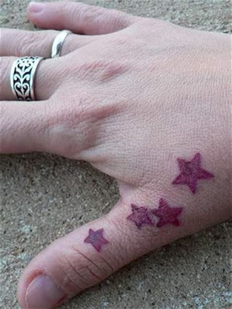 star tattoo on a finger red stars on thumb