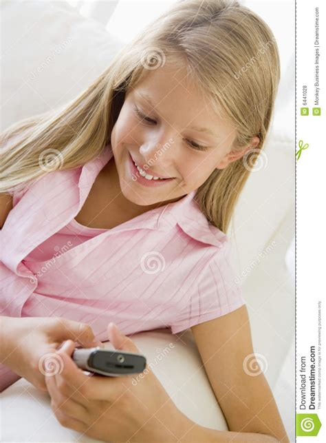 young girls young girl sitting on a sofa texting stock photo image