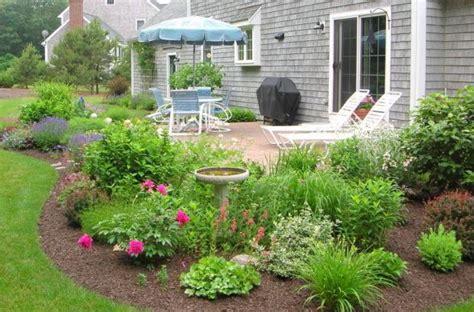 birdbath in planting bed at edge of concrete patio area