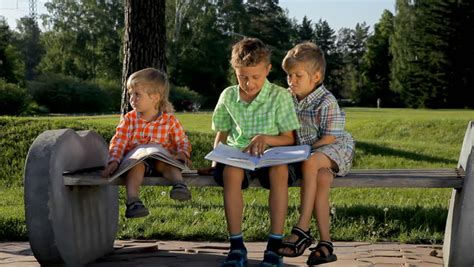 kids reading bench cute boy sitting on a bench in the park and reading the book of tales stock footage