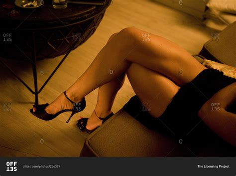 woman in heels sitting with her legs crossed stock photo