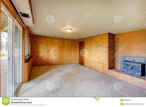 American House Design And Plans empty living room with wood panel walls and cast iron