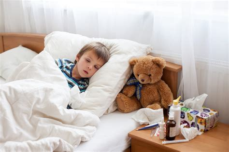sick bed sick child boy lying in bed with a fever resting