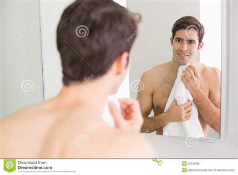 men in the bathroom rear view of man looking at self in bathroom mirror stock