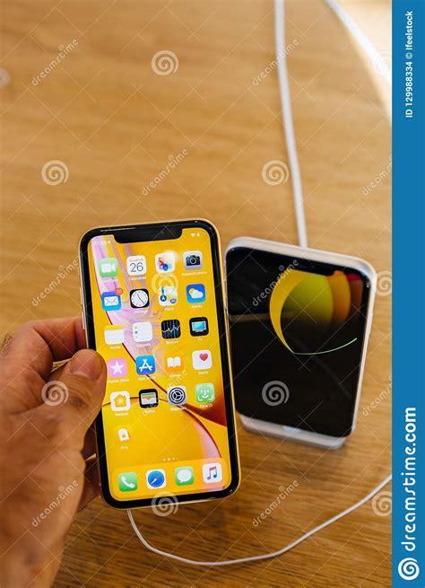 o iphone xr é bom homem que compara o iphone novo xr de apple amarelo contra o branco imagem de stock editorial