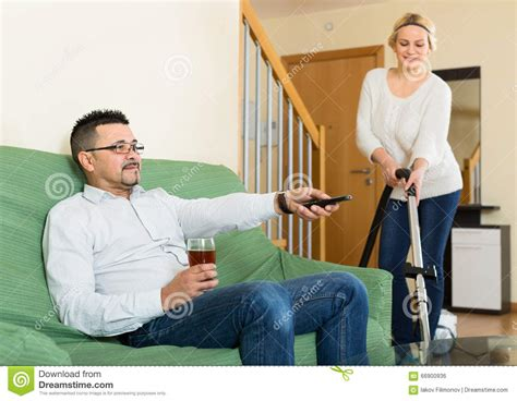 yes man dead on couch man watching tv while woman cleans stock photo image