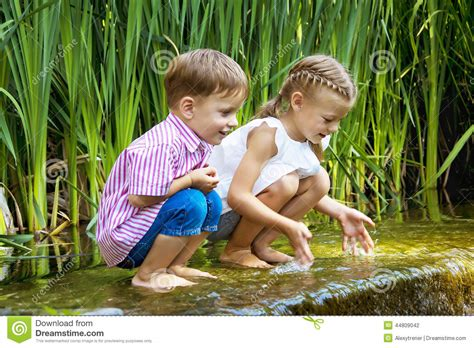Boy And Girl Sitting In Water Near Small Waterfall Stock Picture Of Boy And Free