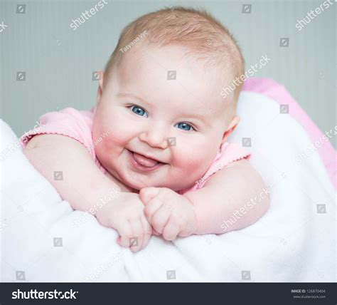 lye in bed cute smiling baby lye on a bed close up stock photo