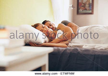 auf dem bett gefesselt ein schlafender mann im bett mit seinem arm stockfoto