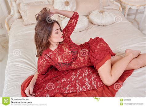 bed dress fashion portrait of elegant young woman in red dress on