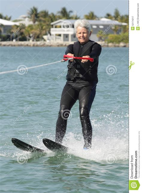 pretty older lady water skiing  nice house stock image