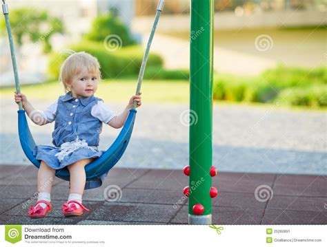 baby on a swing baby swinging on swing on playground side view stock