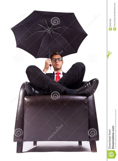 comfortably seated man sitting in comfortable armchair with umbrella stock