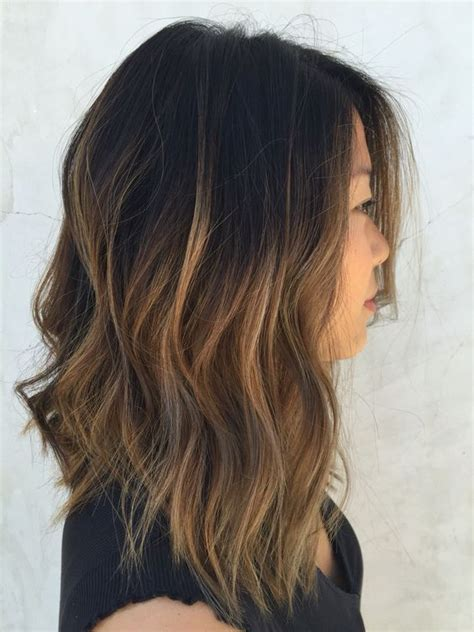 slightly angled long lob picture of textured bob with caramel ombre wavy hair