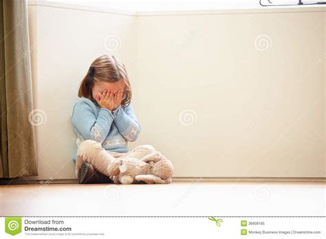 in home sitting unhappy child sitting on floor in corner at home royalty free stock photo image