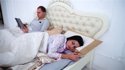 husband and wife bedroom scene cute family sleeping together lying in the bed stock