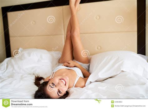 laying down in bed woman lying upside down with legs against headboard stock
