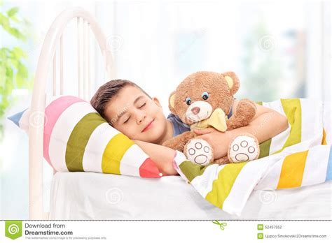 i was comfortable lovely boy sleeping with a teddy bear in a bed stock photo