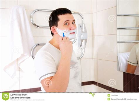 shaving bathroom young man shaving in his bathroom stock photo image
