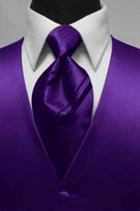 groom in white tux with purple vest but a white tie i