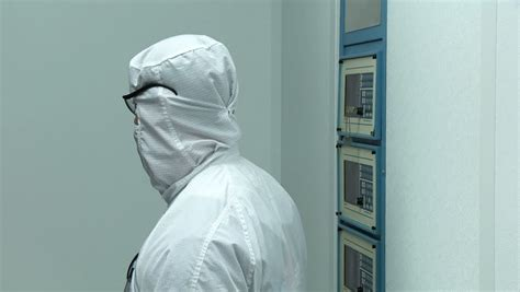 clean room bunny suit technician operating kiln buttons while working on silicon chip manufacture in a clean room