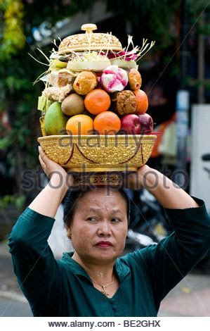 woman with fruit basket on head woman carrying a basket of fruit on her head in mombasa