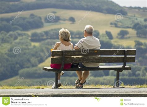 sitting on a bench two older people sitting on a bench stock images image