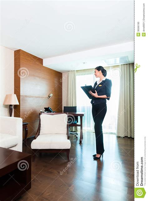 asian executive housekeeper controlling hotel room stock