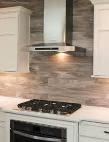 porcelain floor tile with a gray woodgrain pattern is installed as a backsplash in this